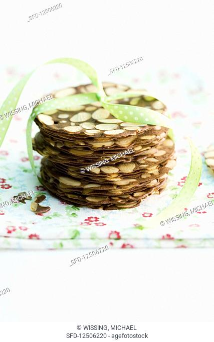 A stack of flaked almond biscuits with ribbon