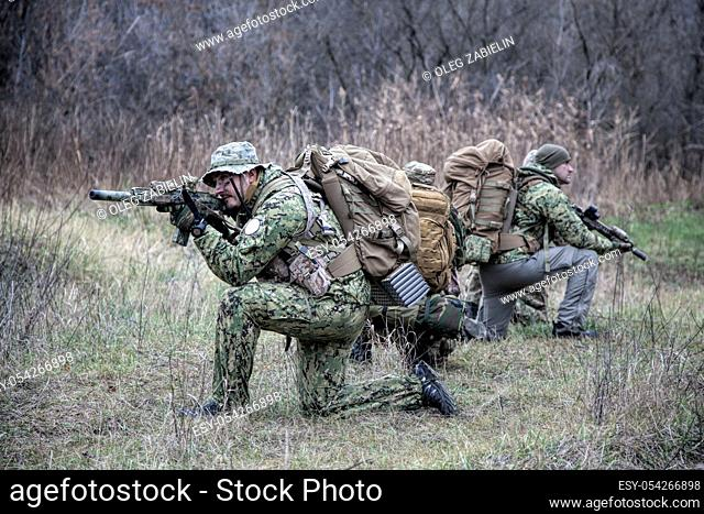 Airsoft, strikeball players team, commando group moving cautiously in forest area, kneeling and looking around, covering comrades, controlling sectors