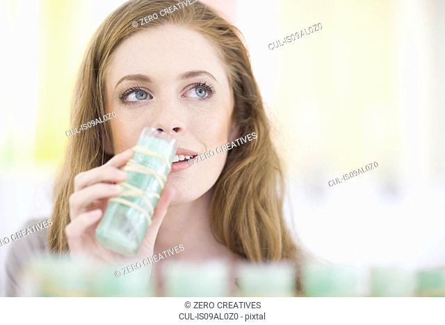 Woman smelling product from display shelf