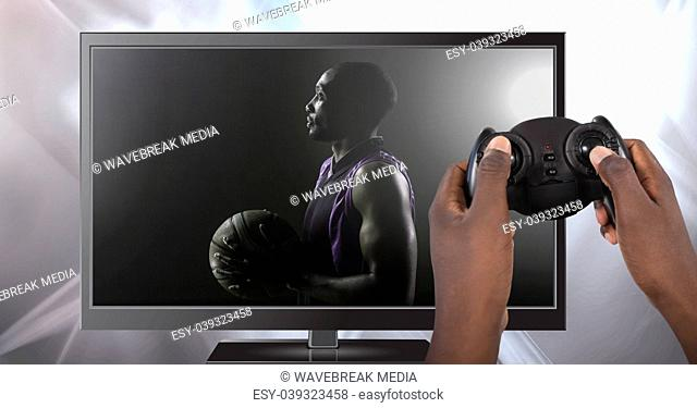 Hands holding gaming controller with basketball on television