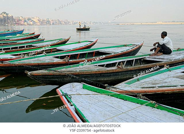Boatman sitting at anchored rowboats at varanasi