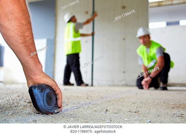 Workers with personal protective equipment, PPE, Marking guide lines for the construction of interior walls, Line tracer, housing construction, concrete