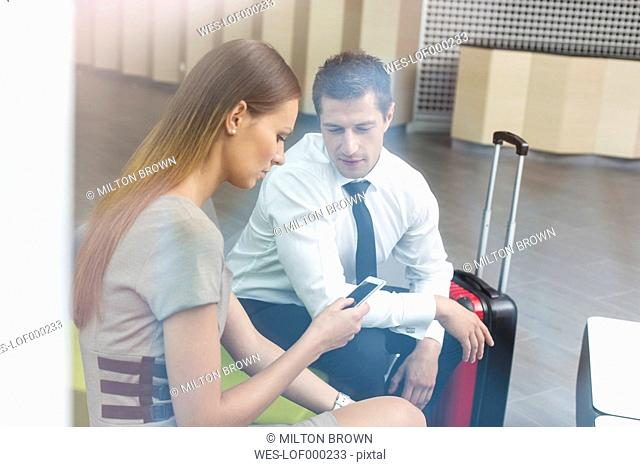 Businessman and businesswoman waiting in hotel lounge