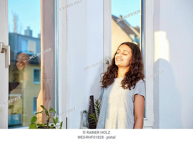 Smiling girl with closed eyes at the window
