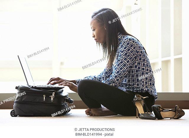 African American businesswoman using laptop on office floor