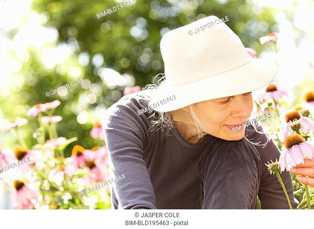 Caucasian woman examining flowers