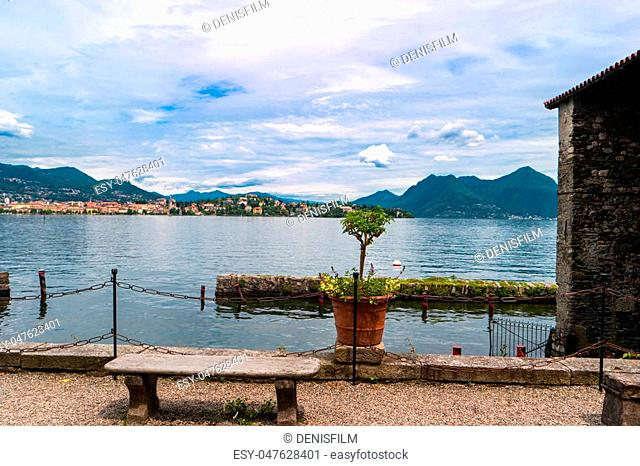 Nature and town buildings. Stone bench near water. Picturesque view of Maggiore lake