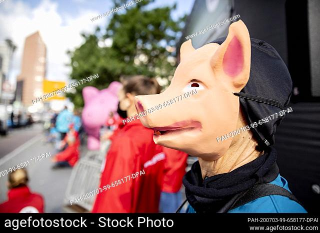 """03 July 2020, Berlin: A person wearing a pig mask takes part in a protest action by animal welfare activists and the animal welfare foundation """"""""Vier Pfoten""""""""..."""