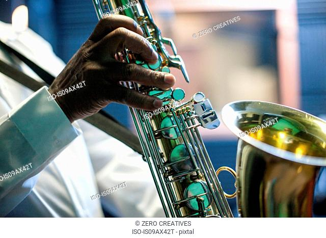 Male musician in recording studio, playing saxophone, mid section