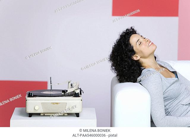 Woman enjoying music, listening to old-fashioned record player