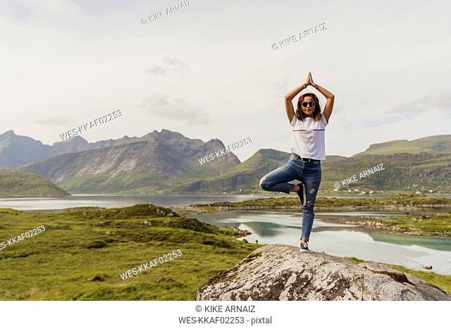 Young woman practicing yoga in nature, Lapland, Norway