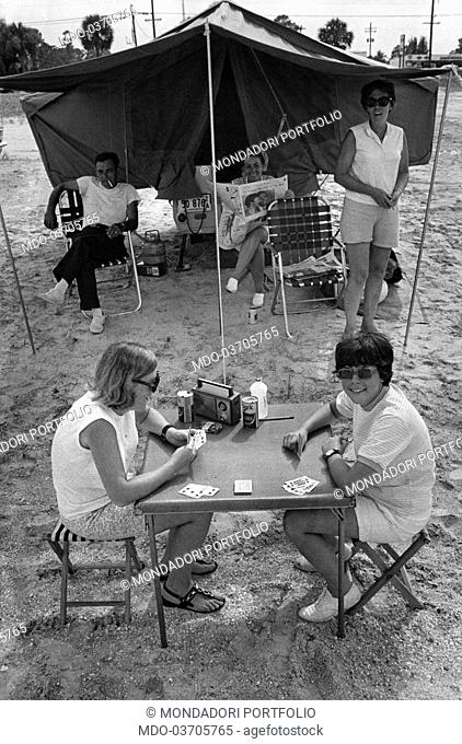 Two girls playing cards on a foldable table while the other members of the family sit in front of a camping tent. USA, July 1969