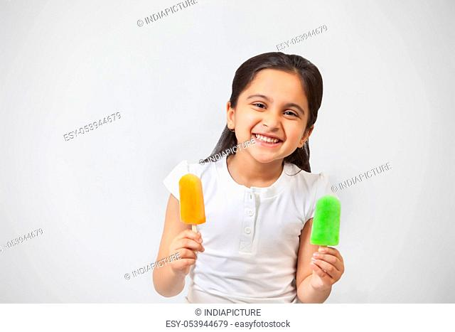 Portrait of happy little girl with ice lollies isolated over gray background