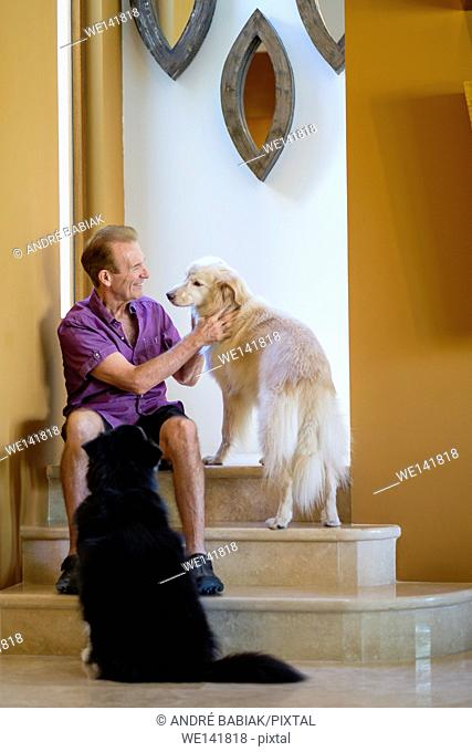 Retired man petting his dogs in his house