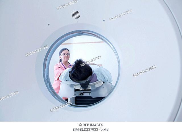 Hispanic nurse comforting patient at scanner