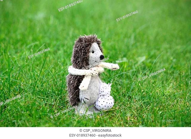 Small cute felt hedgehog standing in the grass