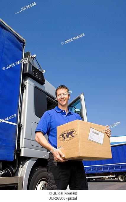 Truck driver standing near semi-truck holding cardboard box