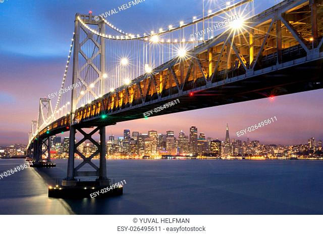 The view of the Bay Bridge lights and the San Francisco skyline creates a fantastic view as seen from Yerba Buena Island in the twilight