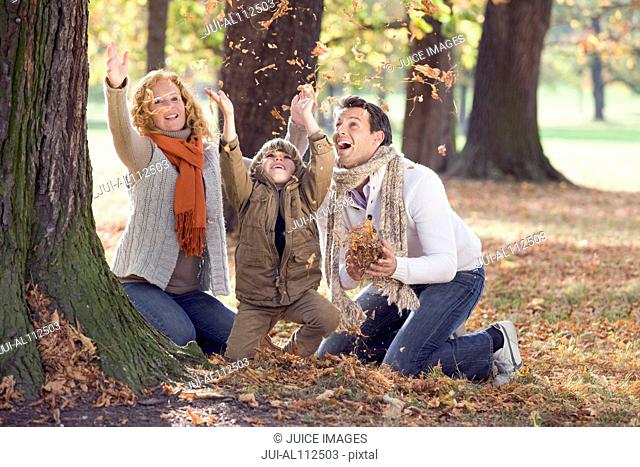 Family playing with leaves in autumn forest