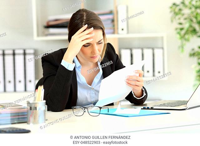 Worried executive reading bad news in a letter at office