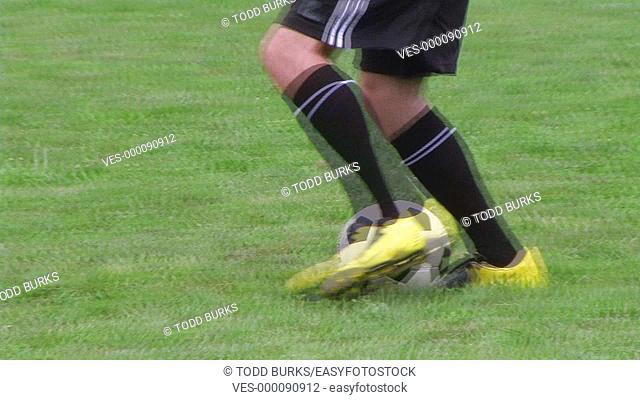Soccer player dribbling ball, dolly shot
