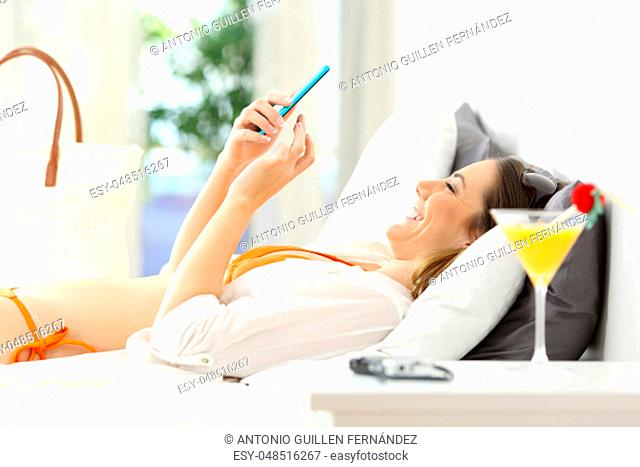Side view portrait of a happy woman using a smart phone lying on a bed of an hotel room on summer vacations