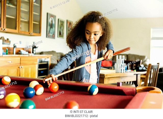 Mixed race girl playing pool