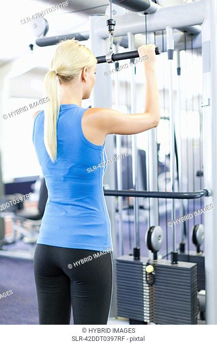 Woman using weights machine in gym