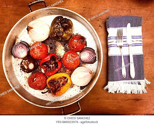 Baked vegetables and a napkin, a fork and a knife in a home in Colonia Roma, Mexico City, Mexico