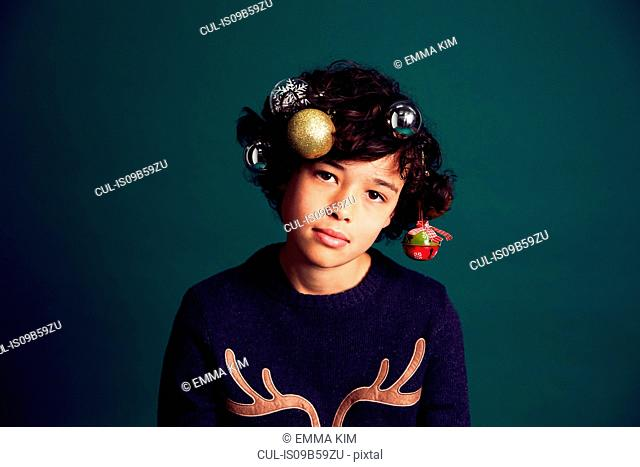 Portrait of teenage boy wearing Christmas jumper, and baubles in hair