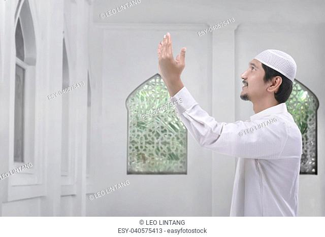 Side view of asian muslim man with traditional dress pray on the mosque