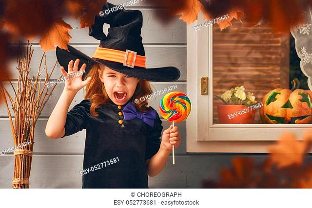 Happy Halloween! Cute cheerful little witch outdoors. Beautiful child girl in witch costume near house decorated to Halloween