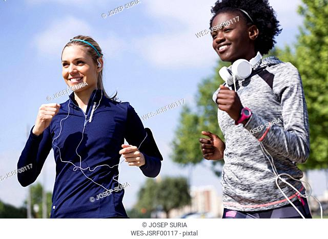 Two happy sporty young women running together in the city