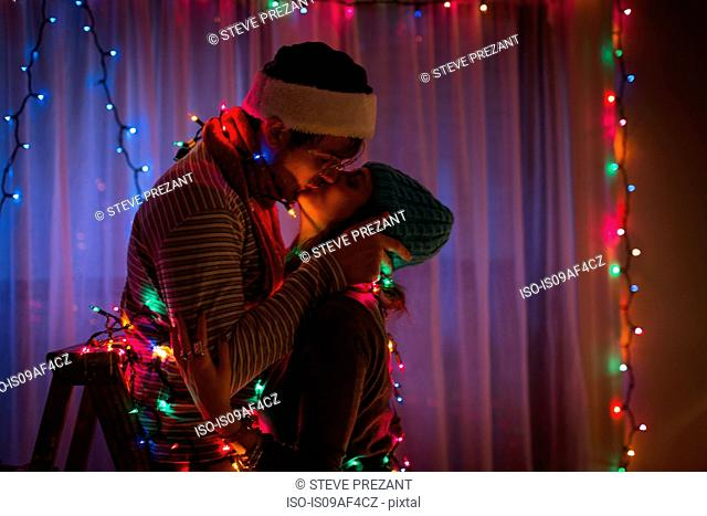 Young couple kissing whilst wrapped in fairy lights at christmas