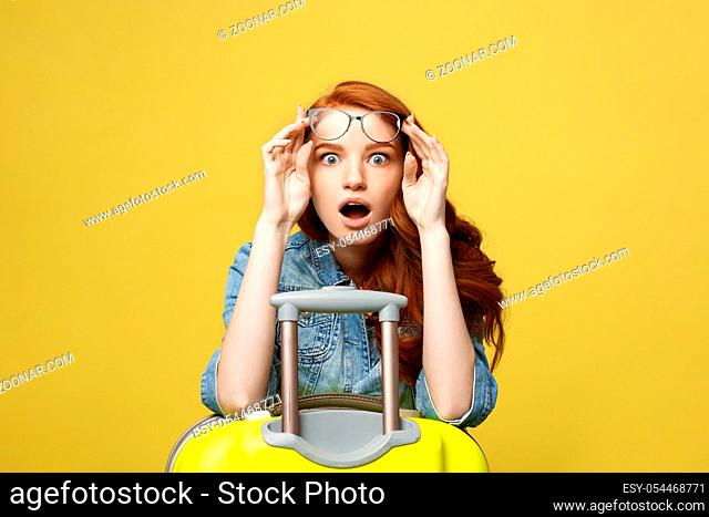 Travel and Lifestyle Concept: Portrait of a shocked girl in denim dress with suitcase looking at camera isolated over golden yellow background