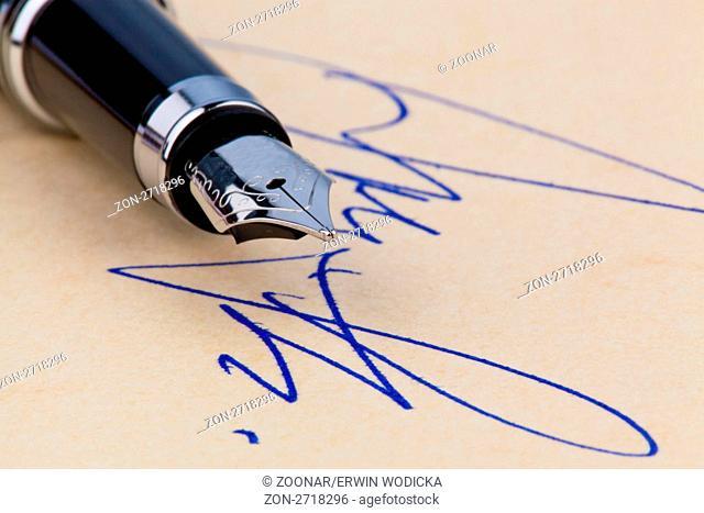 Ein Füllhalter und eine Unterschrift auf gelben Papier. Symbolisch für das Abschließen von Verträgen