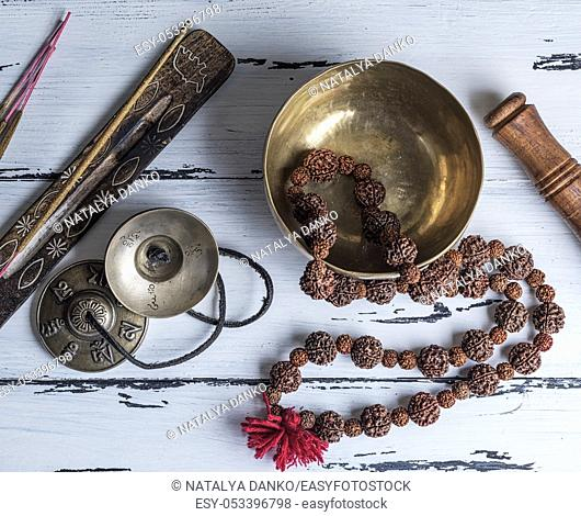 Copper singing bowl and other Tibetan religious objects for meditation and alternative medicine on a white wooden background