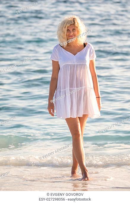 Beautiful woman is standing in water of Indian ocean