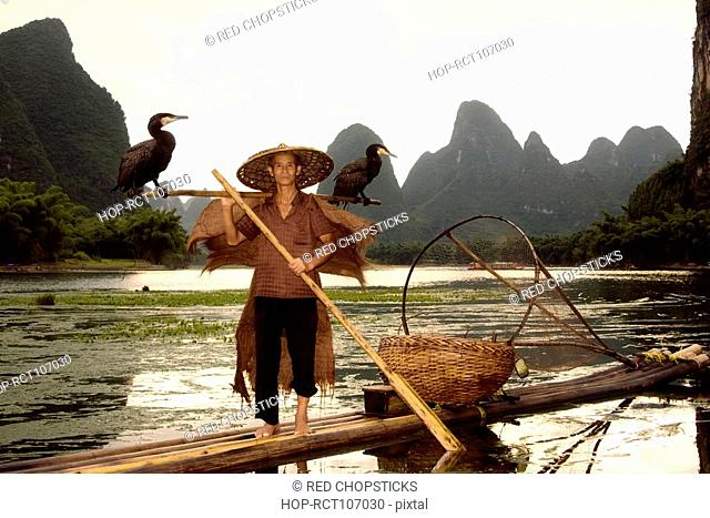 Senior man on a bamboo raft with a hill range in the background, Guilin Hills, XingPing, Yangshuo, Guangxi Province, China