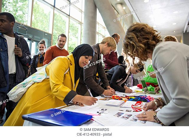 Businesswoman in hijab arriving, checking in at conference registration table
