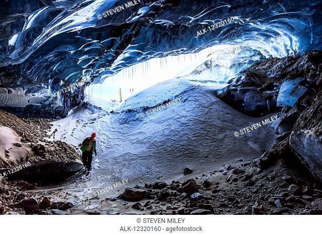 A man enters a cave within Canwell Glacier in the Alaska Range in winter, Interior Alaska, USA