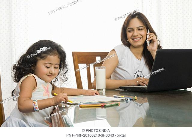 Girl coloring a picture and her mother using a laptop beside her at the dining table