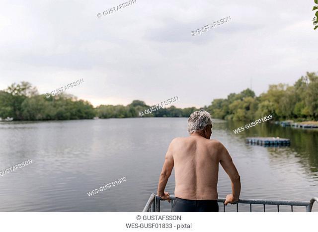 Senior man standing at a lake
