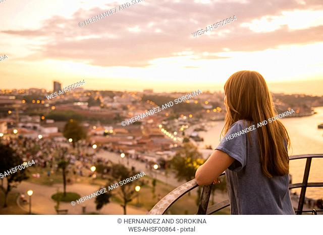 Woman watching panoramic view of Porto at sunset, Portugal