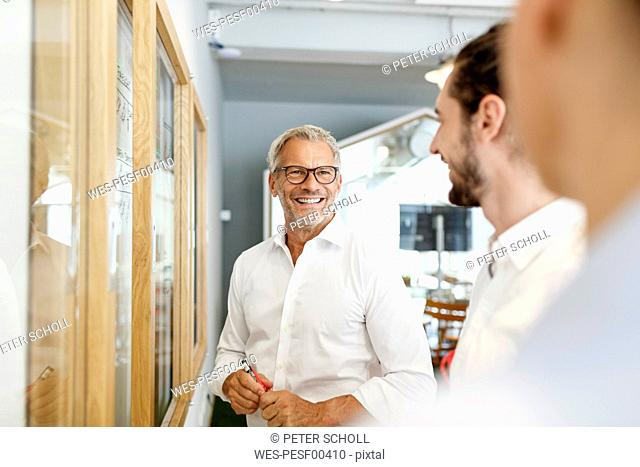 Smiling businessman looking at colleagues in office