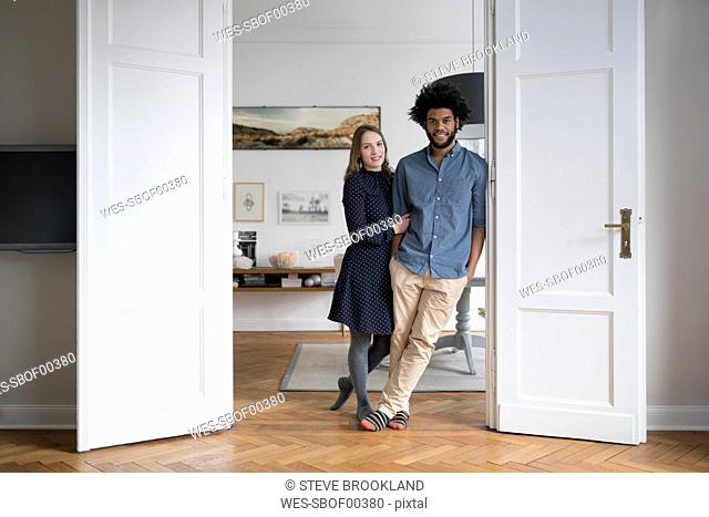 Smiling couple at home standing in door frame