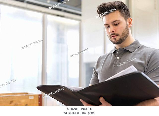 Man looking at folder in factory