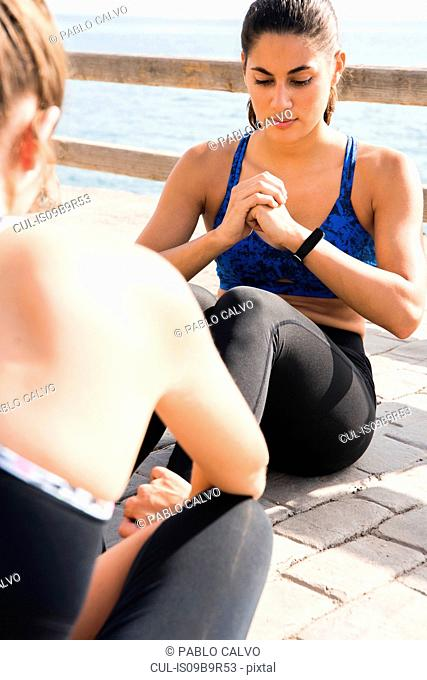 Two young women training together on sea waterfront, doing sit ups