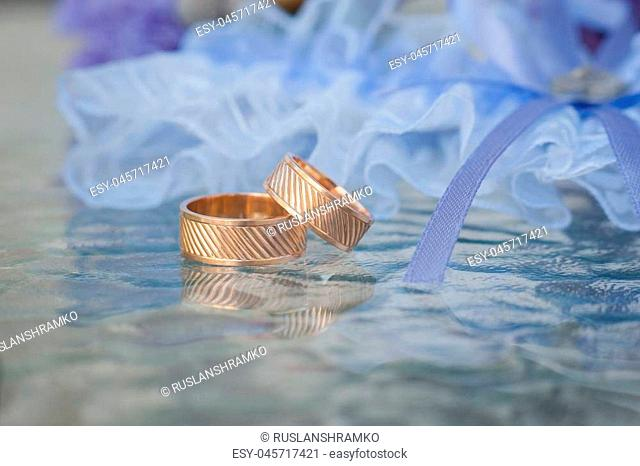 A pair of wedding rings with bokeh background blue garter