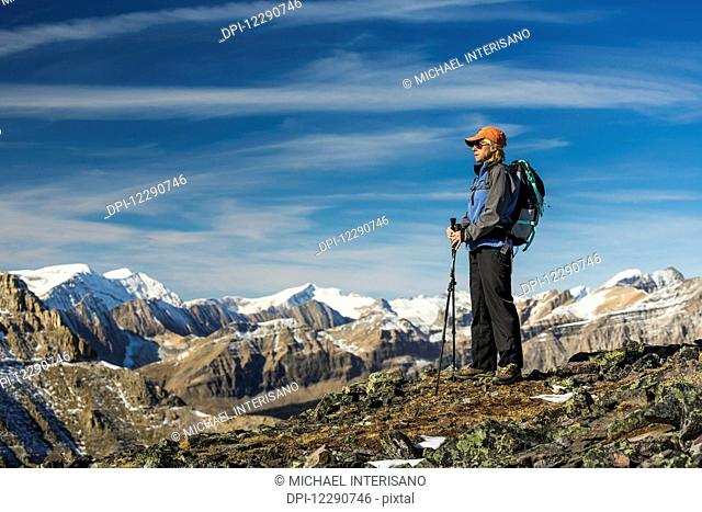 Female hiker with poles standing on top of a rocky mountain ridge overlooking snow peaked mountain ranges with blue sky and clouds, Banff National Park; Alberta